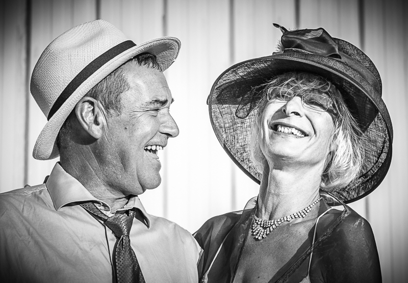 A B&W image of a smiling Georgia & her 'Plus 1' at wedding in France. Her 'plus 1' wears a shirt and tie, the shirt is open at the neck and the tie is slackened. He wears a 'Classic Fedora' style hat with a fine llano weave. Georgia wears an open neck lightweight dress with a square diamond necklace. She also wears a Derby style hat with a large bow on it..