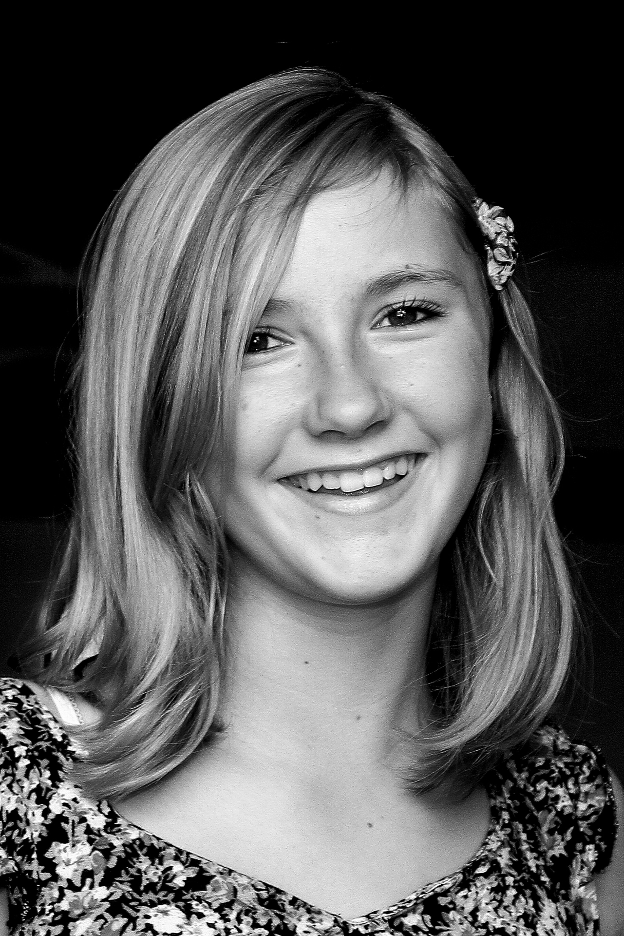 My friends daughter Antonia, seen here smiling in a Black & White head shot. She wears a flowery dress, her long hair is down to her shoulders, and she has a flower in her hair on the LHS.