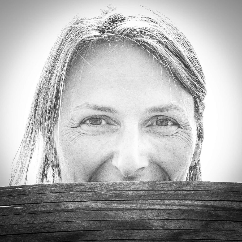 A B&W headshot of the lovely Liz looking over the top of piece of wood. Taken in France in 2011.