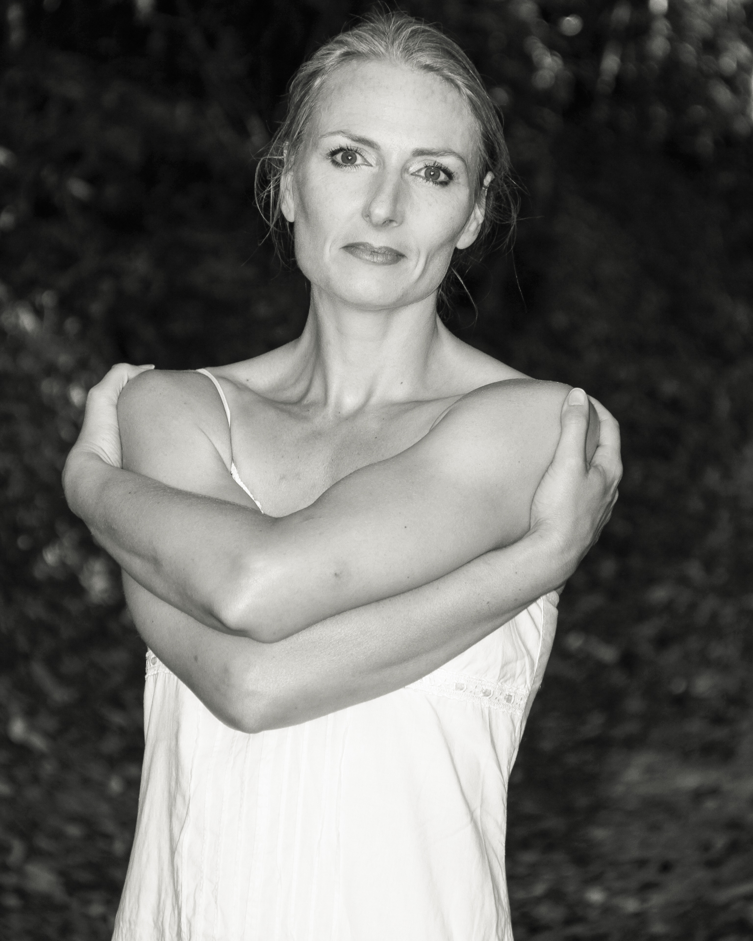 My favourite model Liz in B&W. Liz stands facing the camera, head slightly cocked to her left, arms crossed, and hands on opposite shoulders. She has her hair tied back and wears a lightweight flimsy summer type dress. Taken in France in 2011.