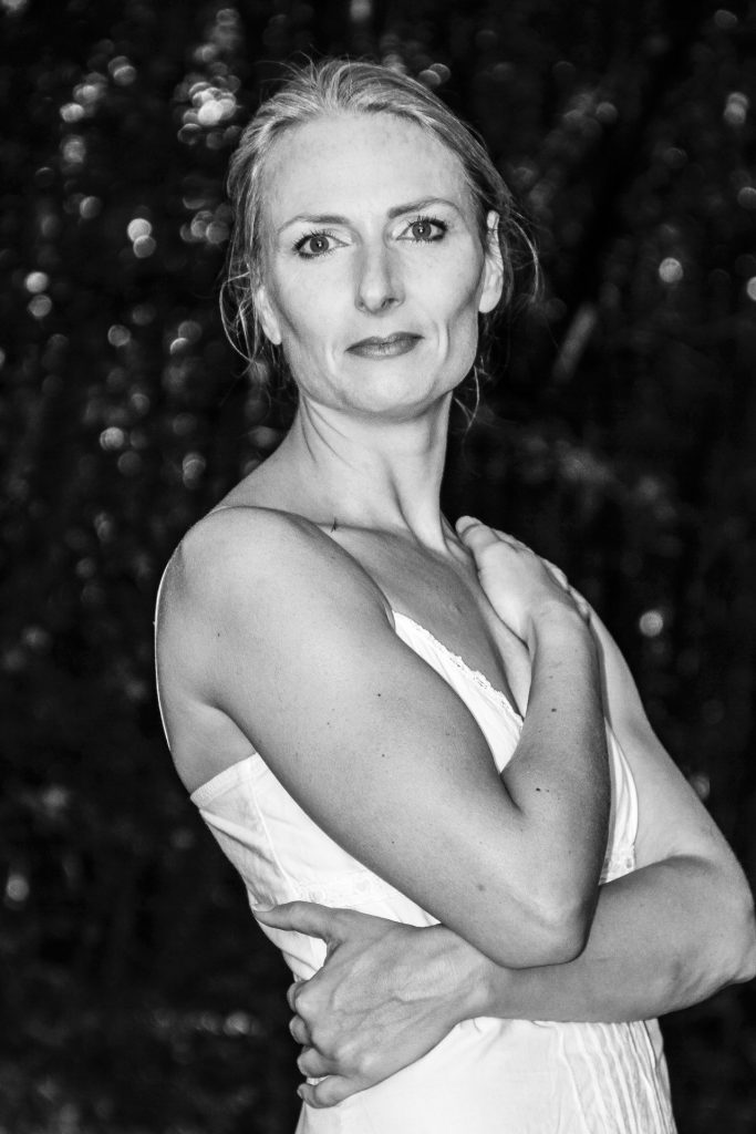Another image of my favourite model Liz. It is in B&W. Liz stands her body facing to the right of the camera, but with her head turned to look directly at the camera. She has her left arm crossed across her waist, and her right arm across her chest with her hand on her opposite shoulder. She has her hair tied back, and she wears a lightweight flimsy dress. Taken in France in 2011.
