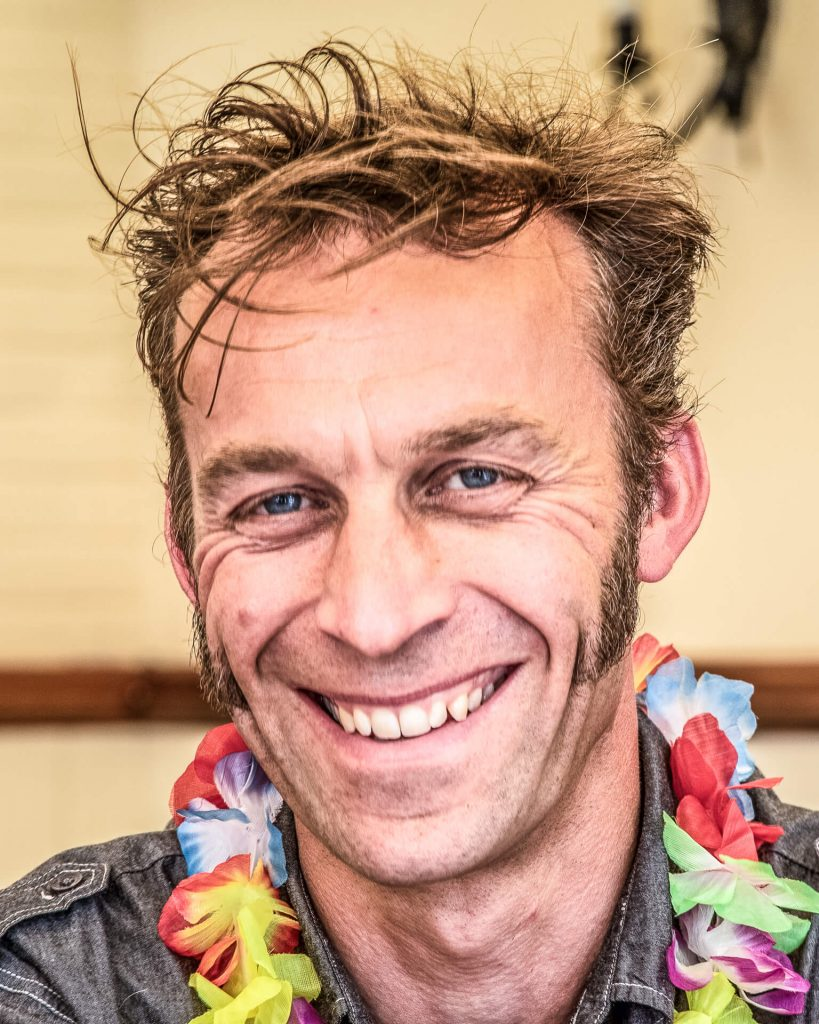 Barry Gammidge in a colour head shot. Barry is seen with a broad grin whilst attending Liz & Dan's wedding. He wears a black denim shirt along with a Lei, a Hawiian style flower garland.
