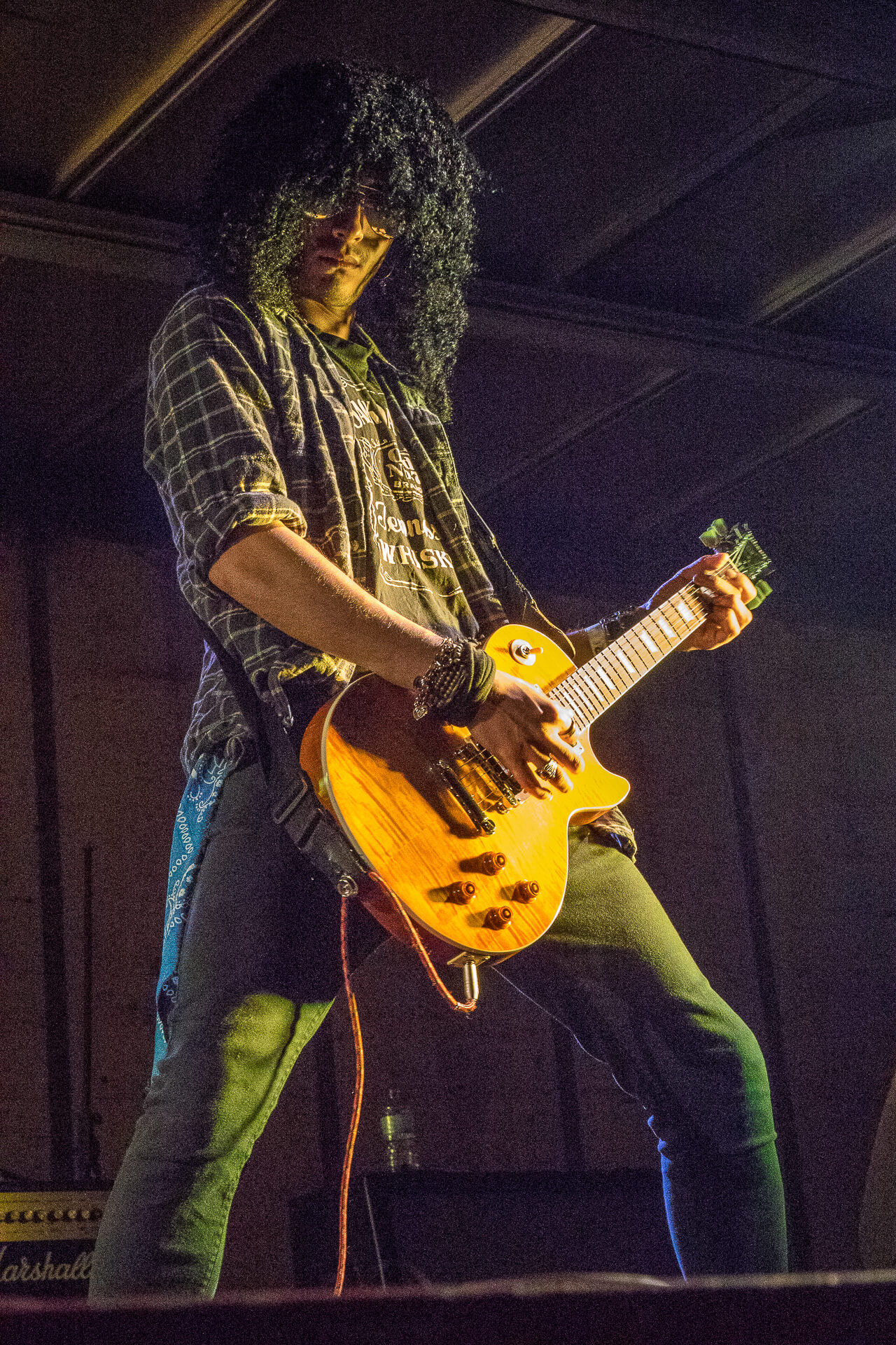 A colour photograph of the Slash lookalike from Guns 2 Roses stood in a classic Slash pose (looking directly at the camera and without his Top Hat) playing guitar on stage at The Drunken Monkey Festival 2017.