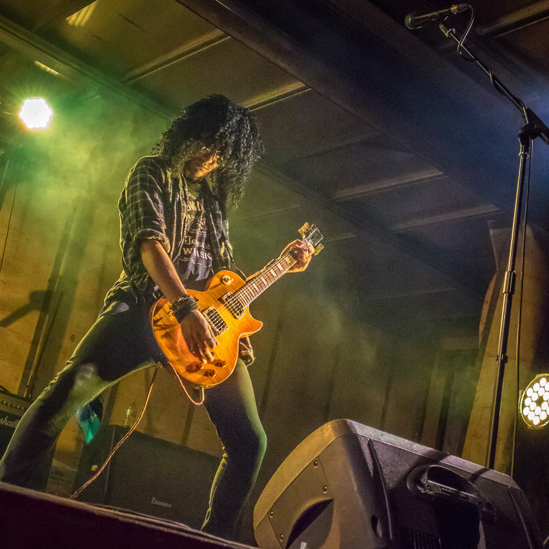 A colour photograph of the Slash lookalike from Guns 2 Roses stood in a classic Slash pose legs wide apart (and without top hat) playing guitar on stage at The Drunken Monkey Festival 2017.