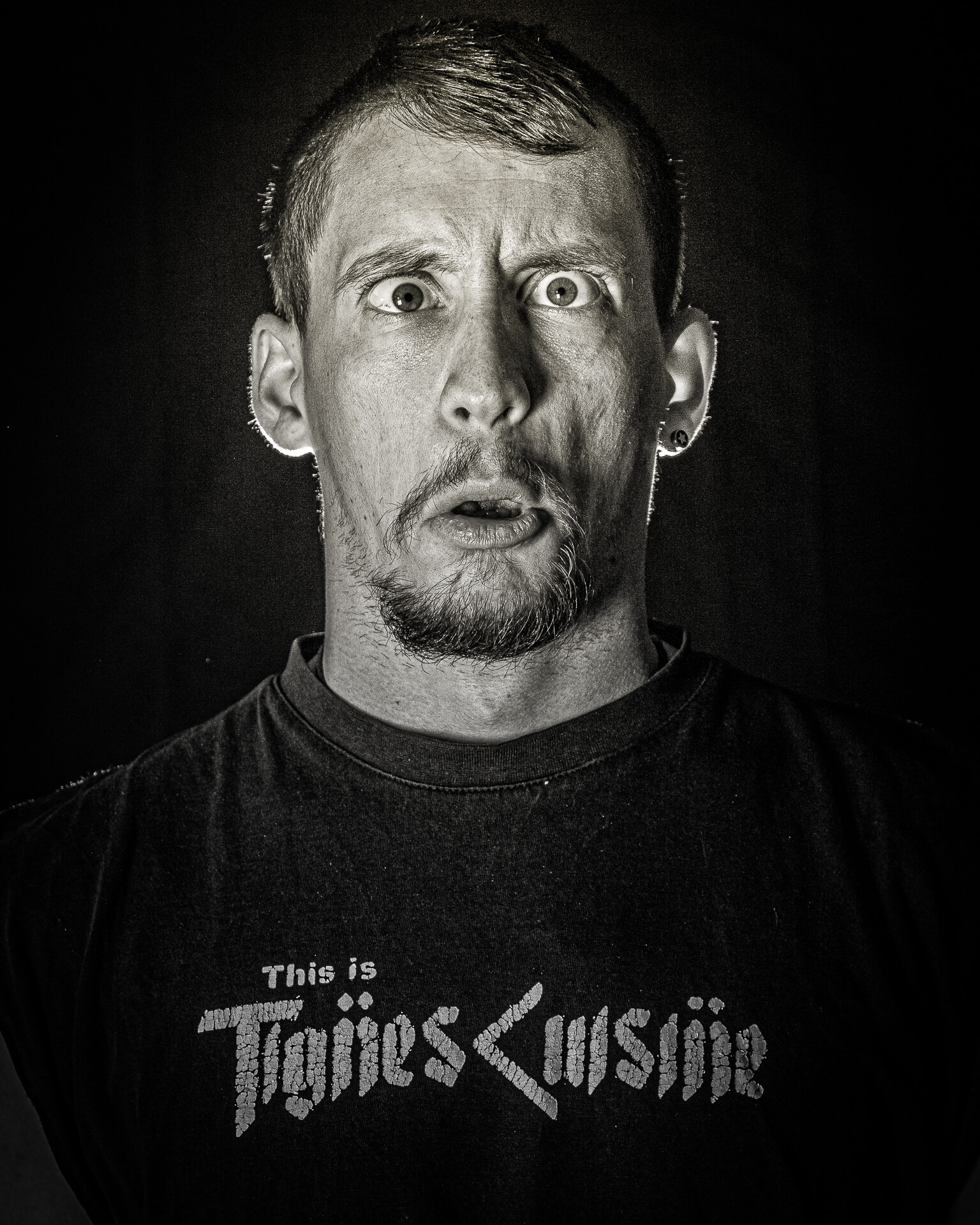 Joel, seen here in a Black & White chest up image pulls a face for the camera. A slightly bearded individual, his mouth is slightly open, whilst his left eye is wide open and looks ahead, his right looks inward.