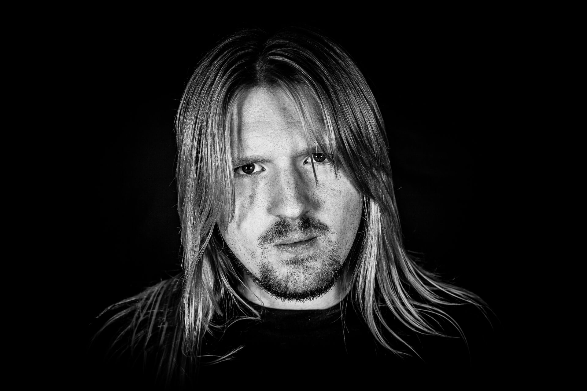 A moody Black & White headshot of Miles Meakin. Miles plays guitar with the British rock band Midnite City.