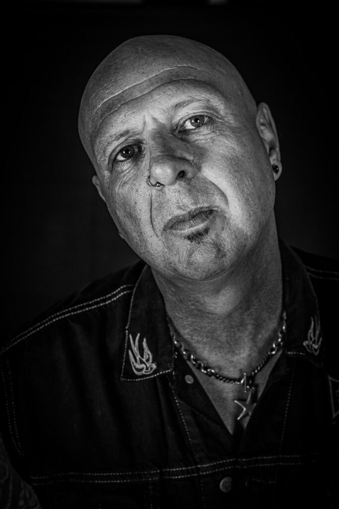 A head & shoulders image of drummer & music producer Pete Newdeck. Seen in Black & White Pete has his head tilted to his RHS and he stares straight into the camera.