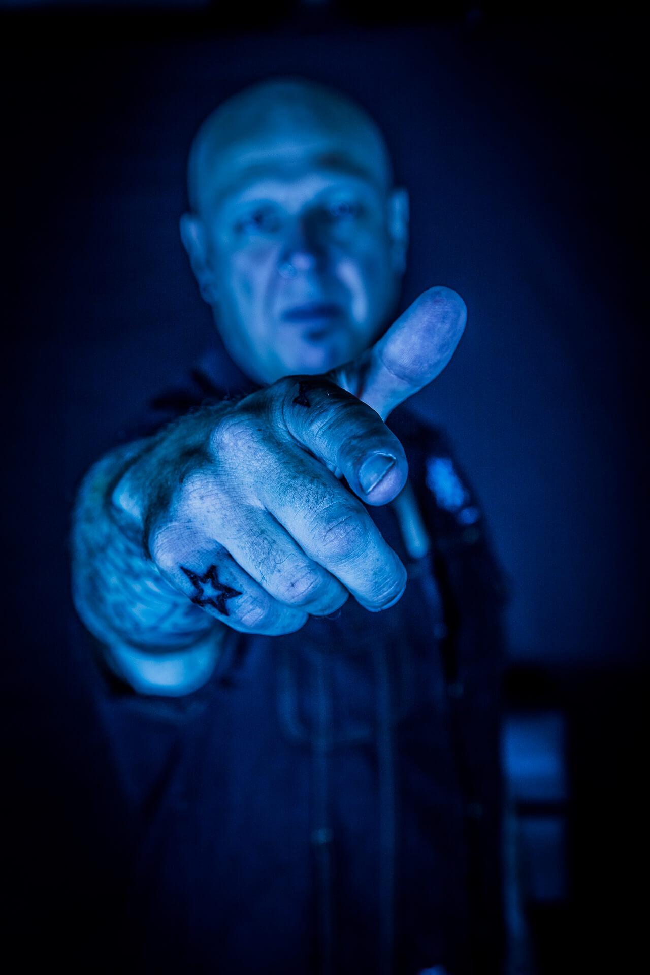 A blue tinted shot of drummer & producer Pete Newdeck, pointing at the camera. Only his outstretched fingers are in focus, the rest of him is slightly out of focus.