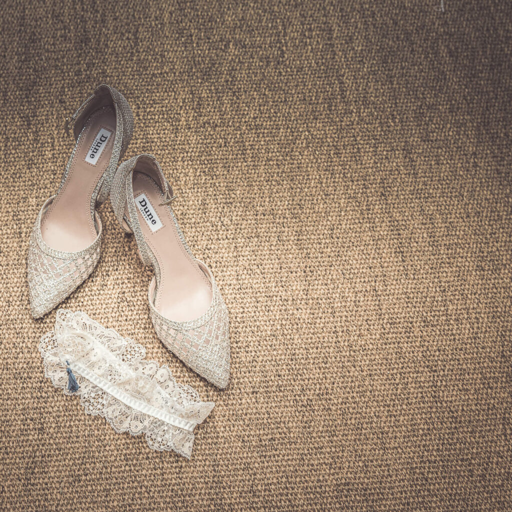 The Bridal Shoes & Garter ready to be worn. They are of a beige colour.