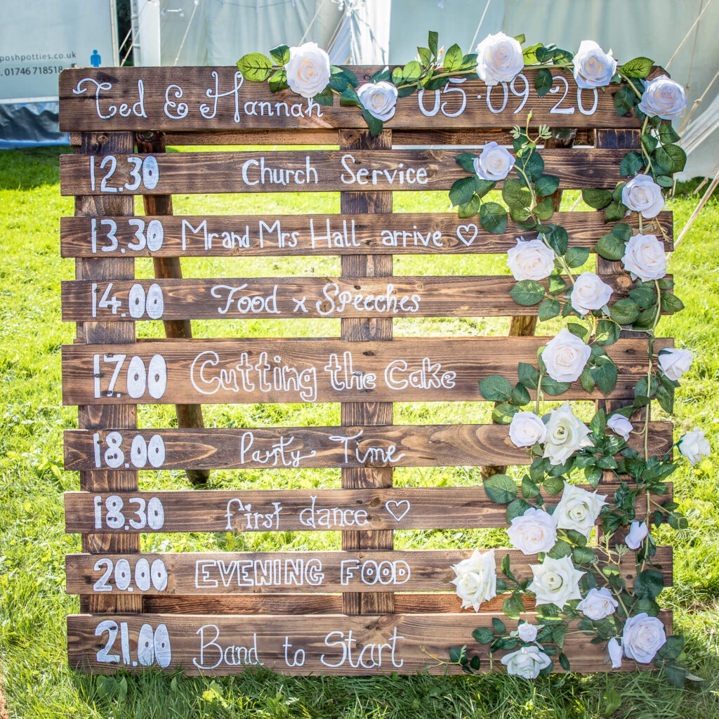 The hand written reception time plan ingeniously displayed on a pallet outside of the reception entrance, decorated with light pink roses.