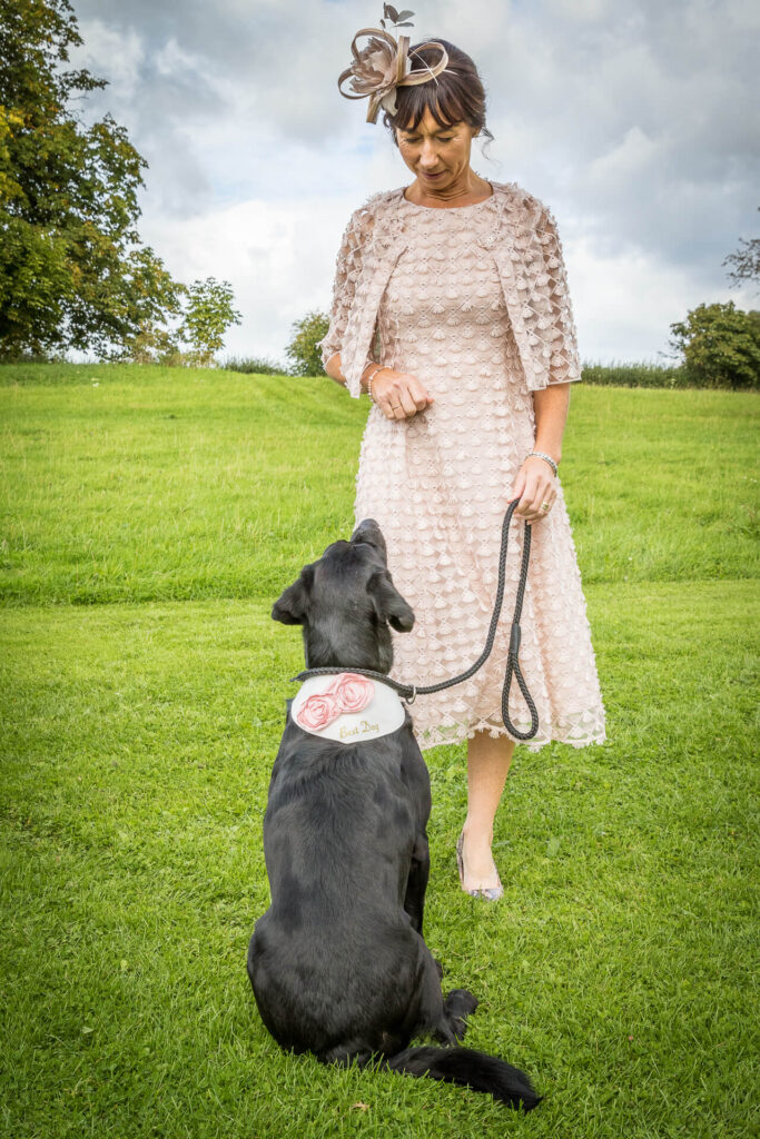 The Best Dog (a Black Labrador) wearing his Best Dog collar sits on a grassy bank, in front of and looking up at the Mother of the Bride who holds his slack lead in her left hand. She has a clenched right hand, suggesting that he is being blackmailed to behave with treats.