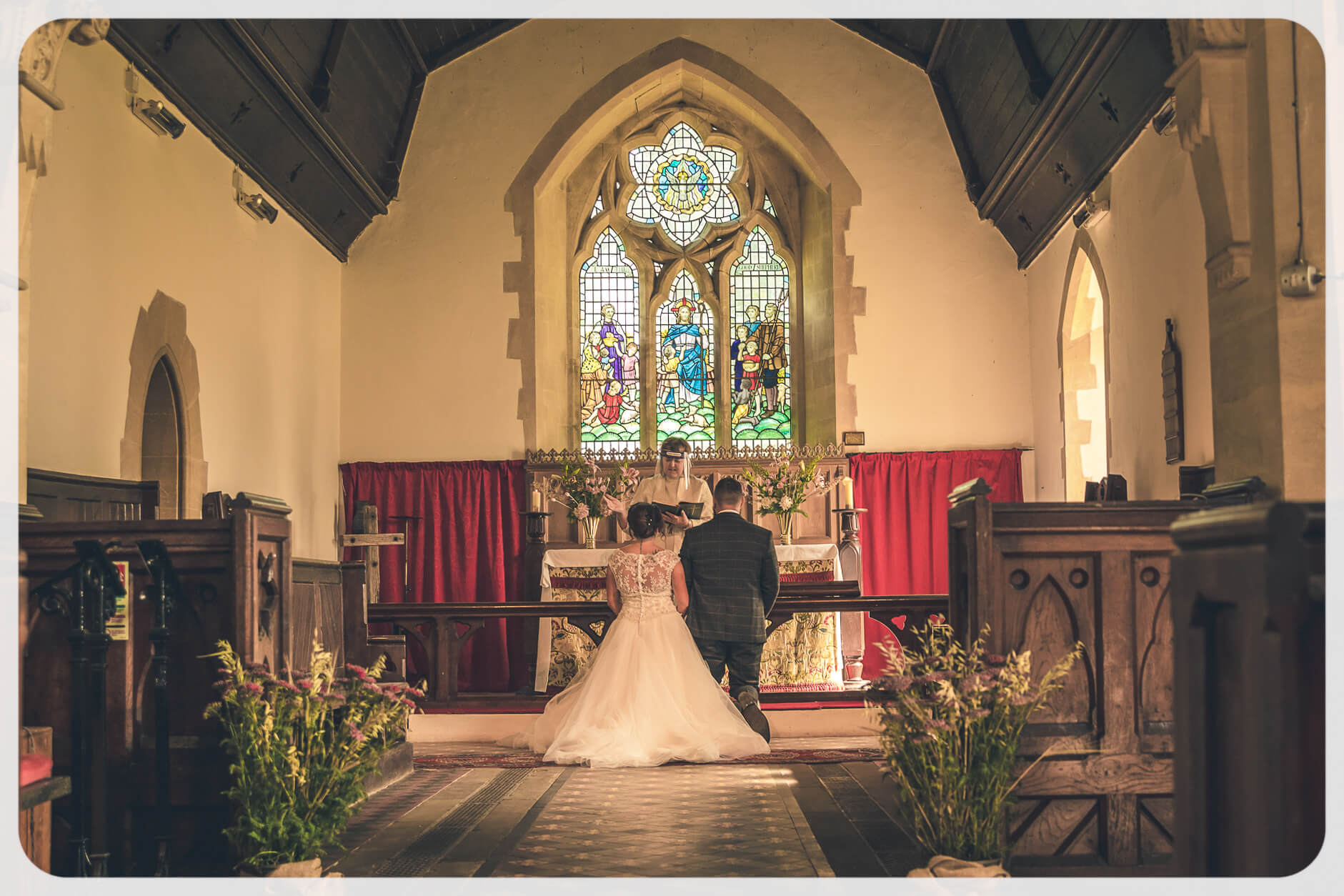 The Bride and Groom kneel at the alter in front of the female priest as she reads out part of the wedding service. The priest wears a full face shield as required by COVID regulations at the time.