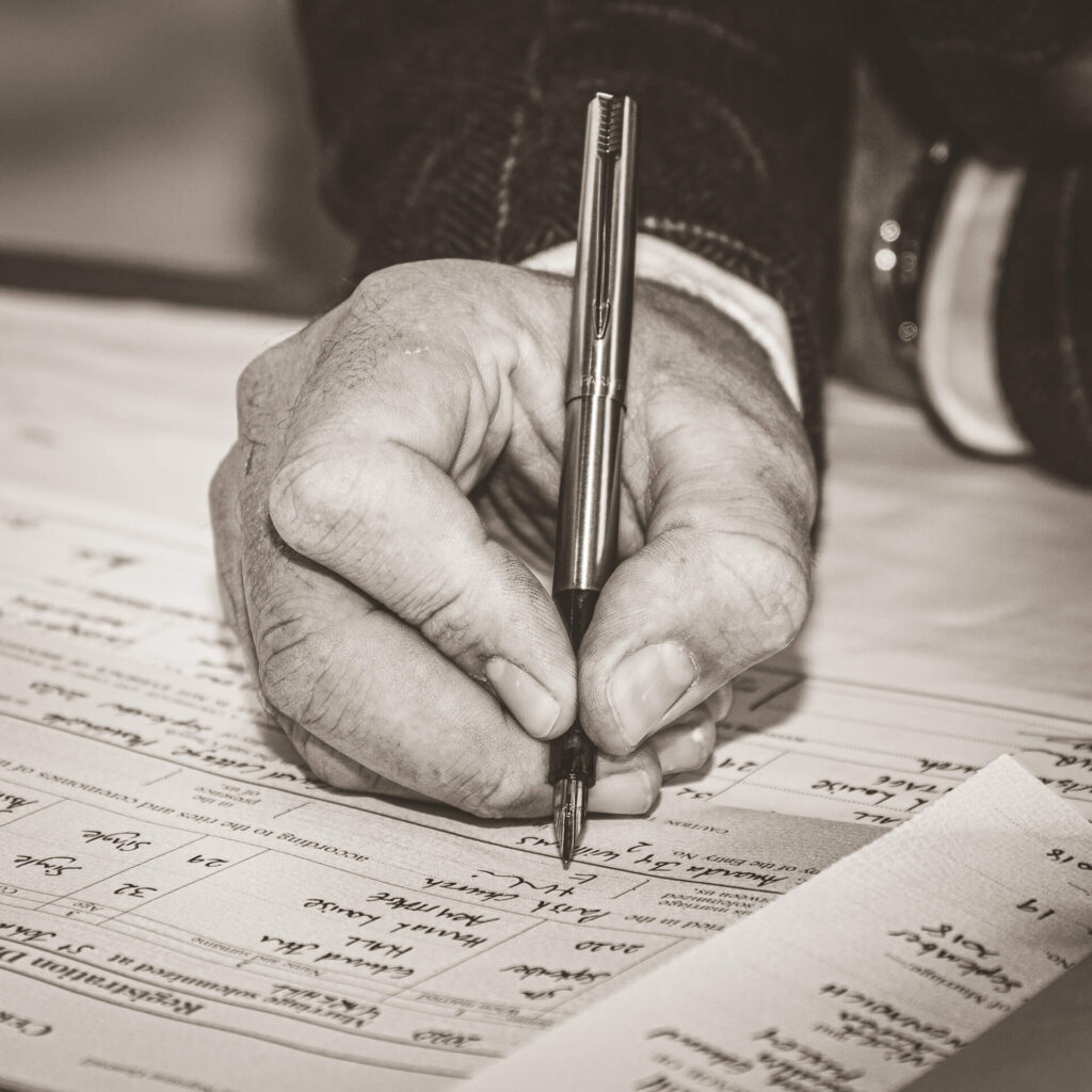 A sepia style close-up shot of the Grooms hand as he signs the register with a fountain pen.