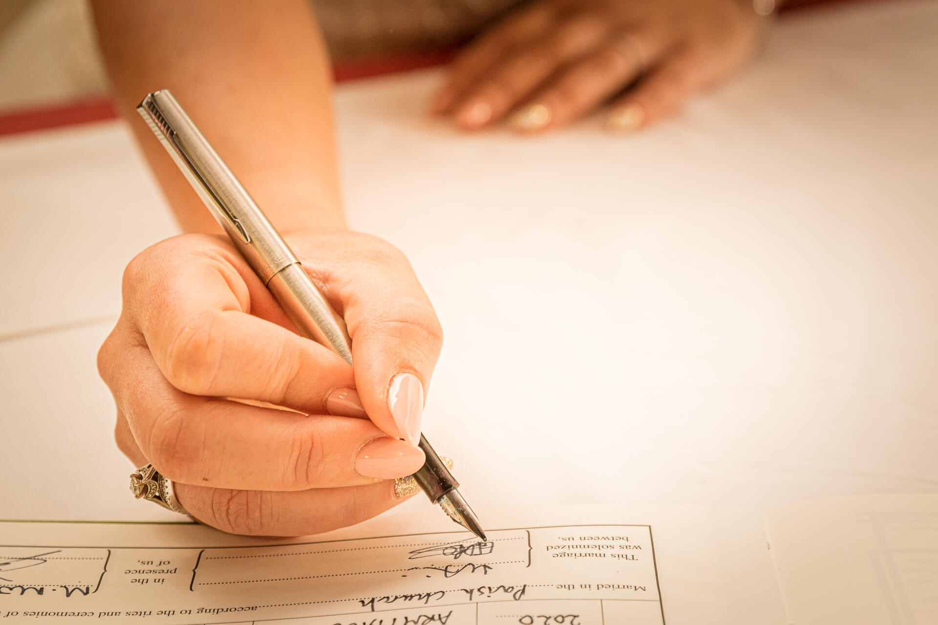 A close-up shot of the hand of the Bride holding an ink pen as she signs the marriage register.