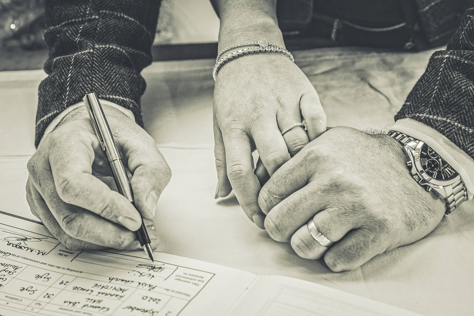 A close up shot of the Grooms hands as he signs the wedding register with a fountain pen. The Bride holds his left thumb with her left hand, both wedding rings are visible.