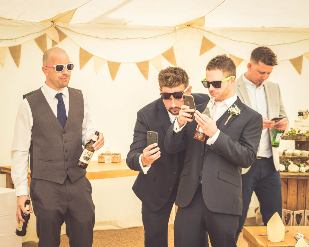 3 male wedding guests act the fool at the reception.  2 are wearing novelty sunglasses whilst staring at their mobile phones, and another also wearing sunglasses holds 2 bottles of beer.