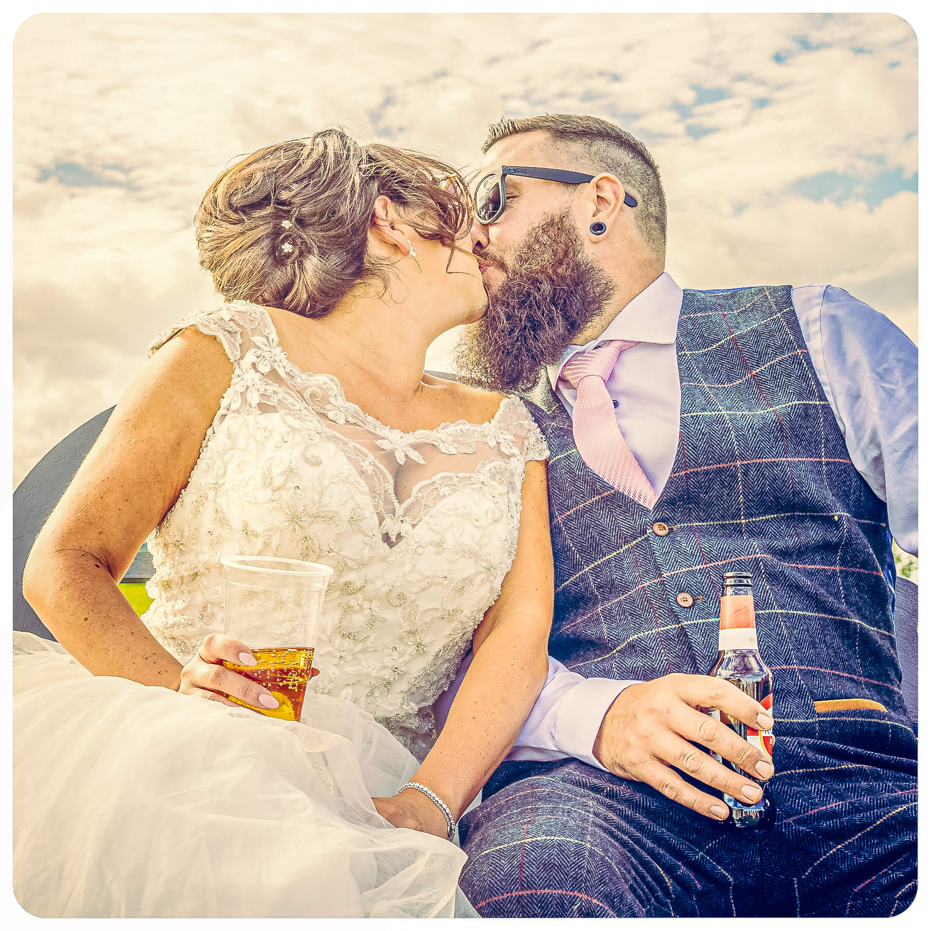 The Bride & Groom share a kiss whilst taking a break during the formal photographs. Both have the obligatory drink in their hand.