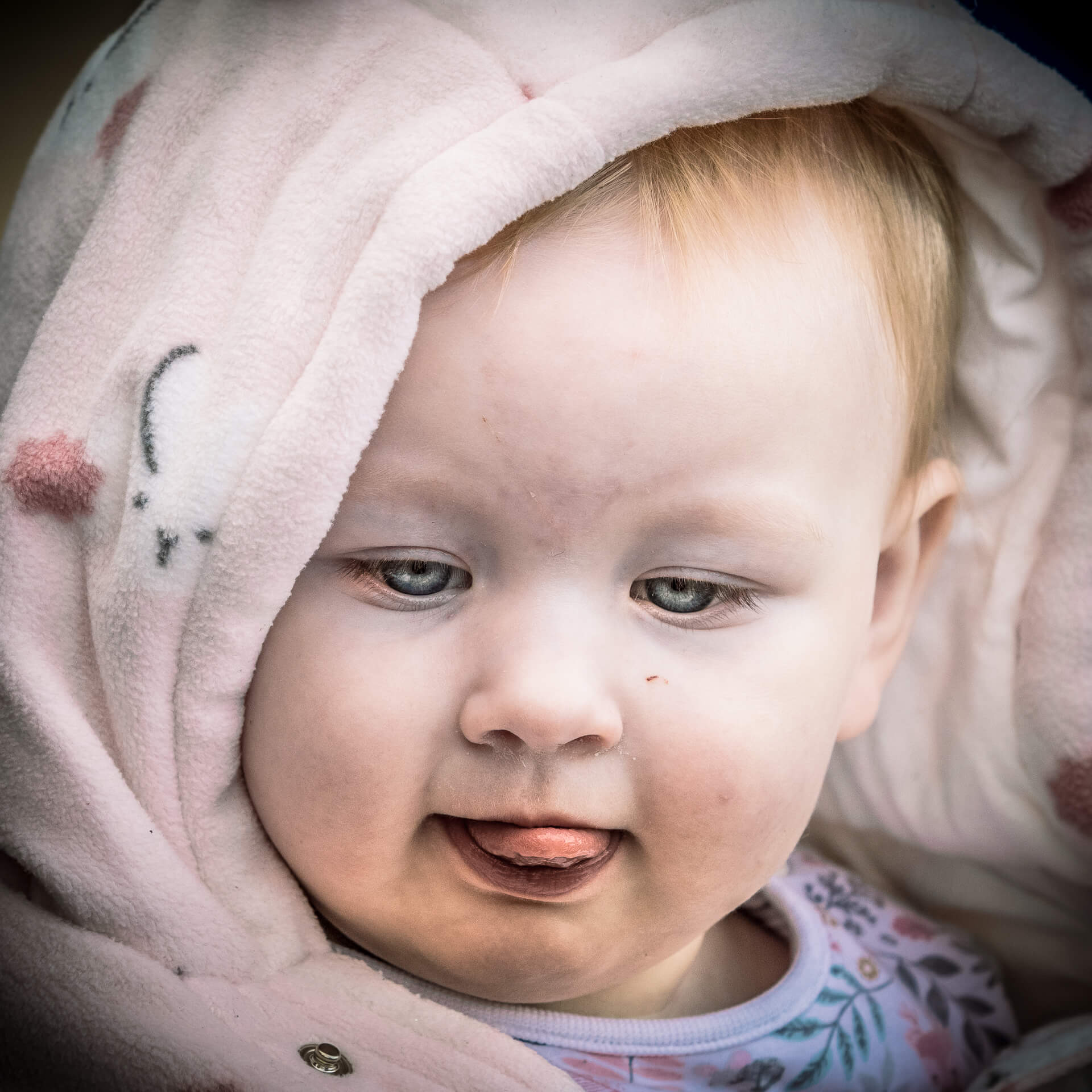 This image shows a blue eyed baby intently looking at something just below the camera. The baby is seen (in a head only shot) in a pink coloured hooded fleece, and she is sticking her tongue out.