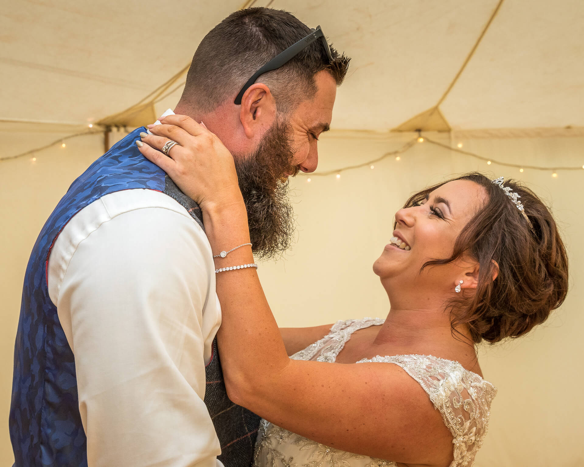 The bearded Groom having dispensed with his jacket and with sunglasses on top of his head, holds his new wife by the waist as they smile and gaze into one another eyes. She has her hands around the sides of his neck.