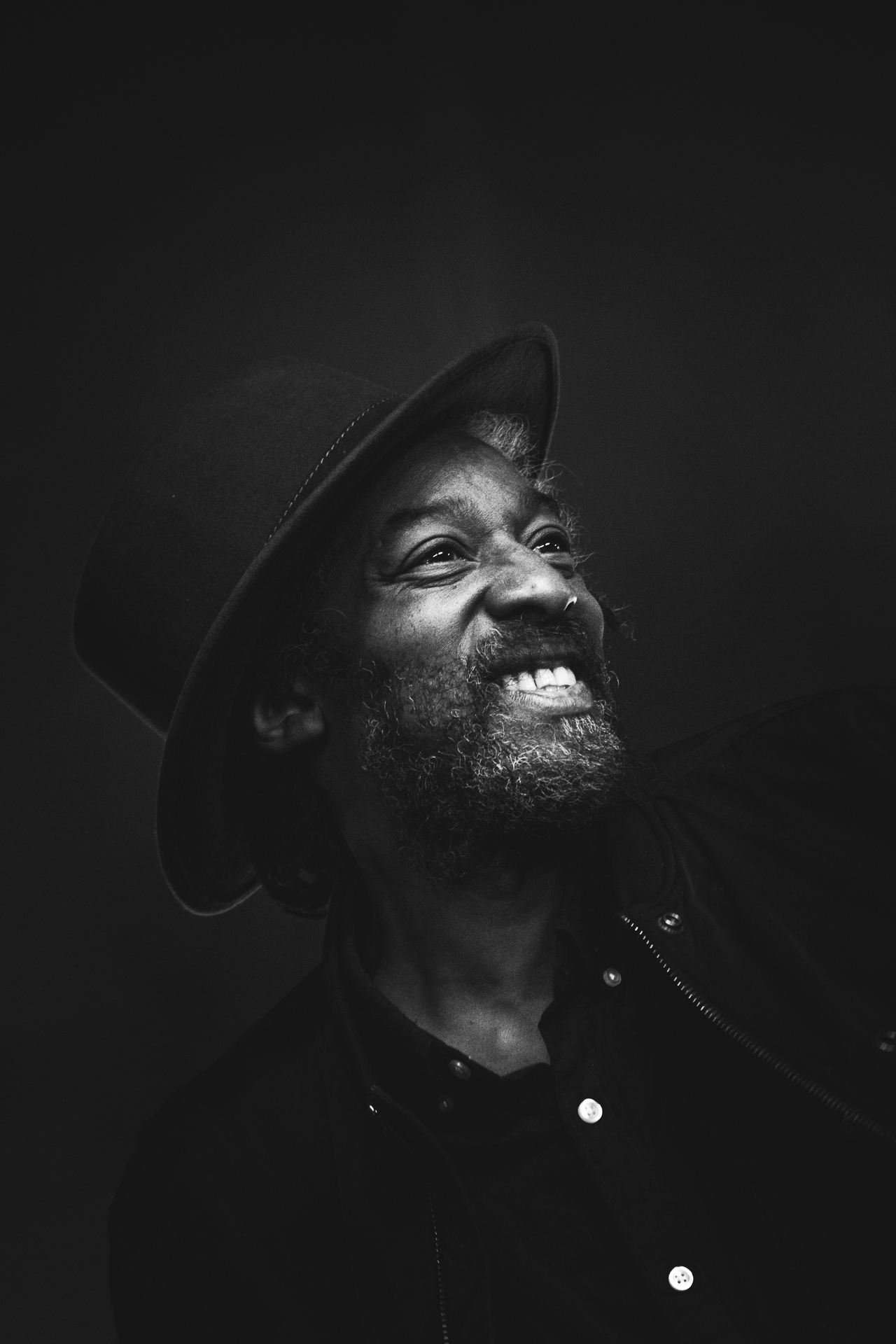 """A chest and head shot of Angus """"Drummie Zeb"""" Gaye. Angus is the Drummer, Vocalist and founder member of the Reggae group Aswad. He is seen here (smiling) whilst on stage with the band at Lakefest 2018."""
