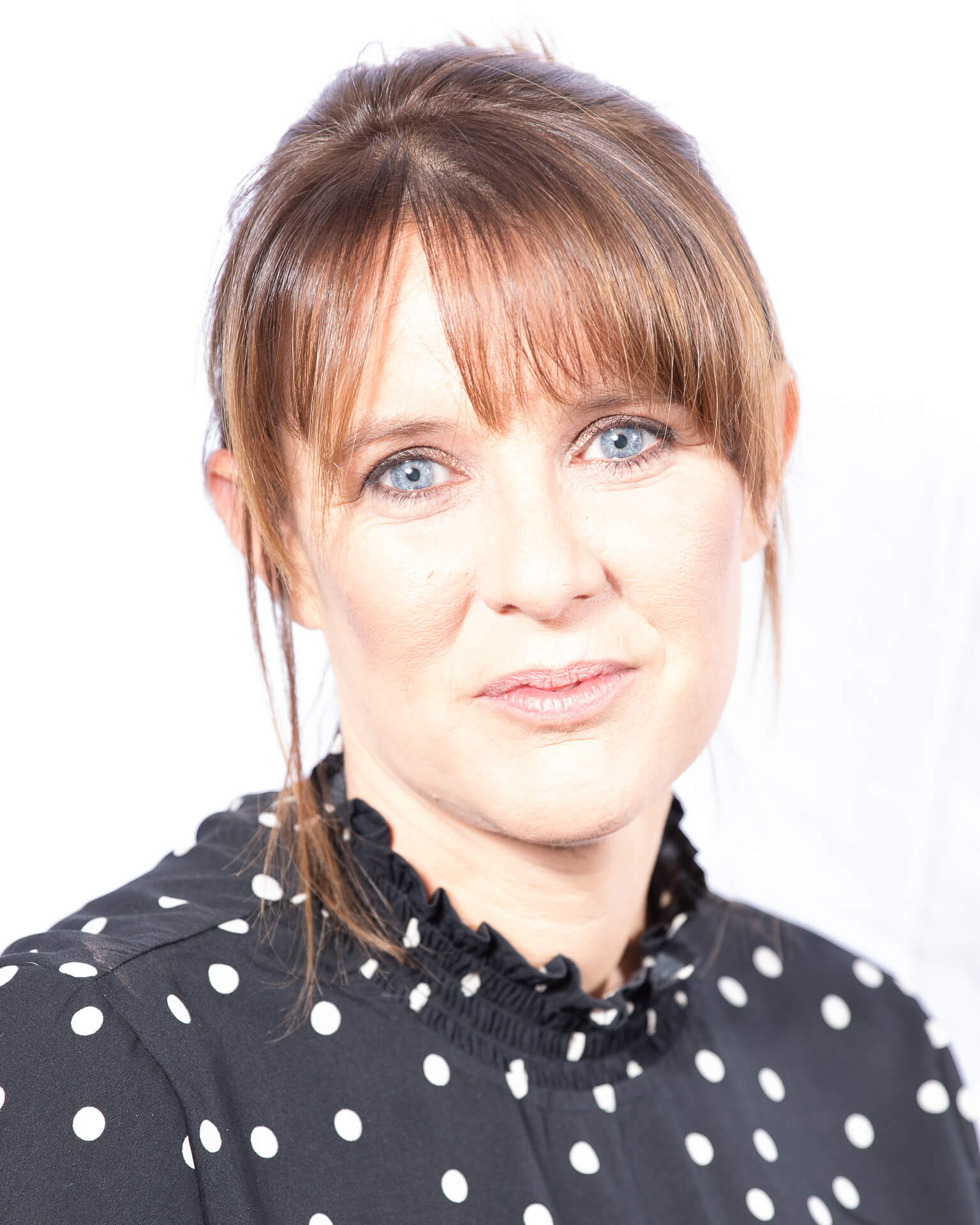 This colour head and shoulders image shows Sarah. Sarah poses in a 'typically standard' formal workplace type pose; she looks directly into the camera. Sarah has vivid blue eyes and is wearing a white spotted black top. Sarah is employed by a funeral directors.