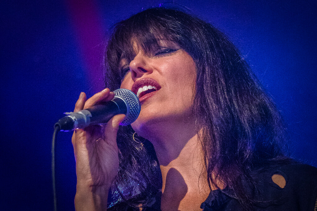 A colour headshot photograph taken at Lakefest 2017 of Imelda May singing an emotional song whilst on stage.