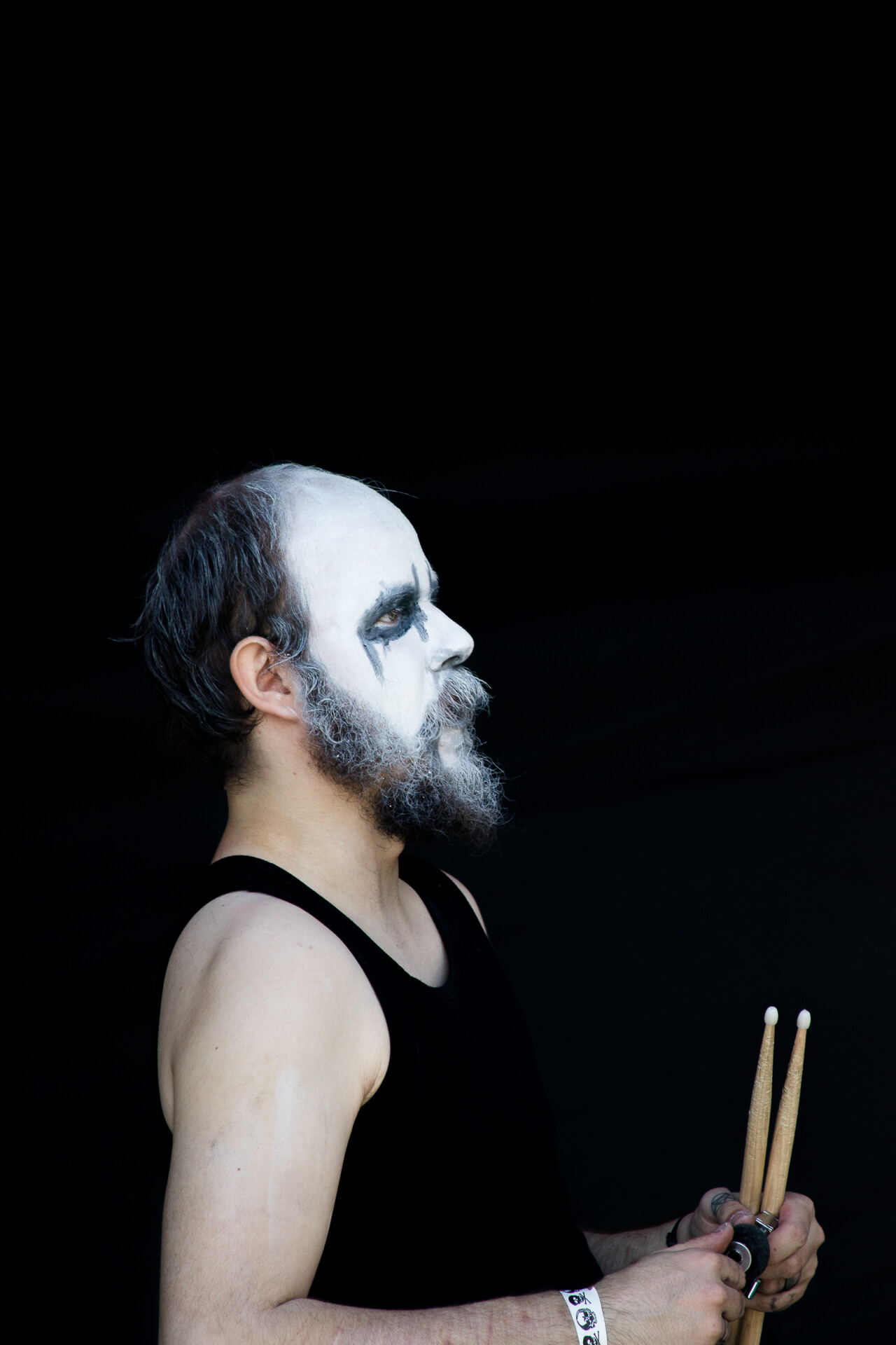 A colour image, waist up, taken against a pure black background, of a drummer waiting to go on stage at The Drunken Monkey Rock Festival. The festival is held each year in Upton Upon Severn to raise funds for The Midlands Air Ambulance. He wears a singlet vest, he sports a full beard and moustache and holds his drumsticks in front of him. His whole face is made up white and short black lines have been applied, the site emphasises his beard.