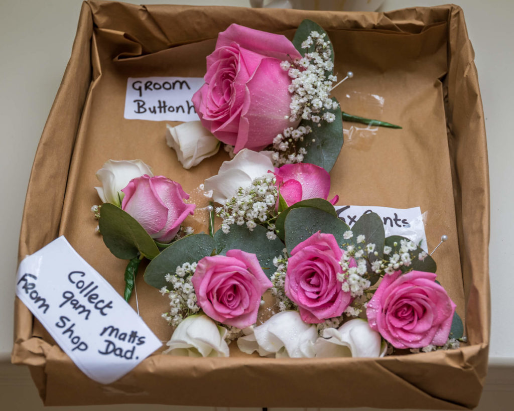 The Grooms Party Buttonholes. A box of buttonholes for the Grooms Party consisting of Pink/Cerise Roses.