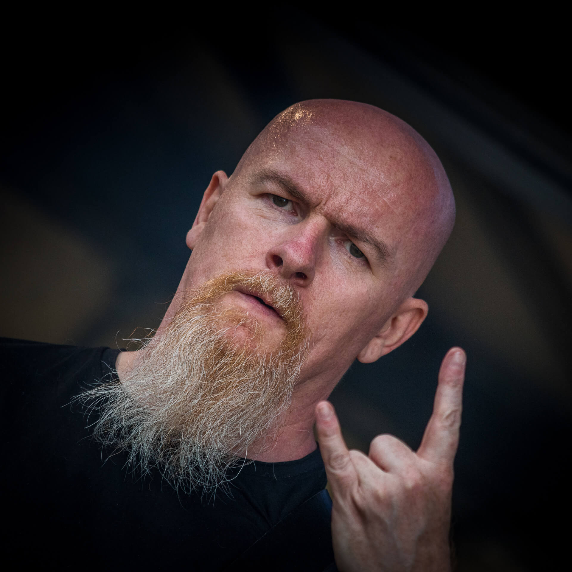 A colour head and shoulders photograph of Glyn Shepherd (The Bassist in Vulcan Raine) as he looks directly at the camera with left hand raised level with his beard in a 'Heavy Metal Devils Horns' pose at The Drunken Monkey 2017 whilst performing with Sabbotage.