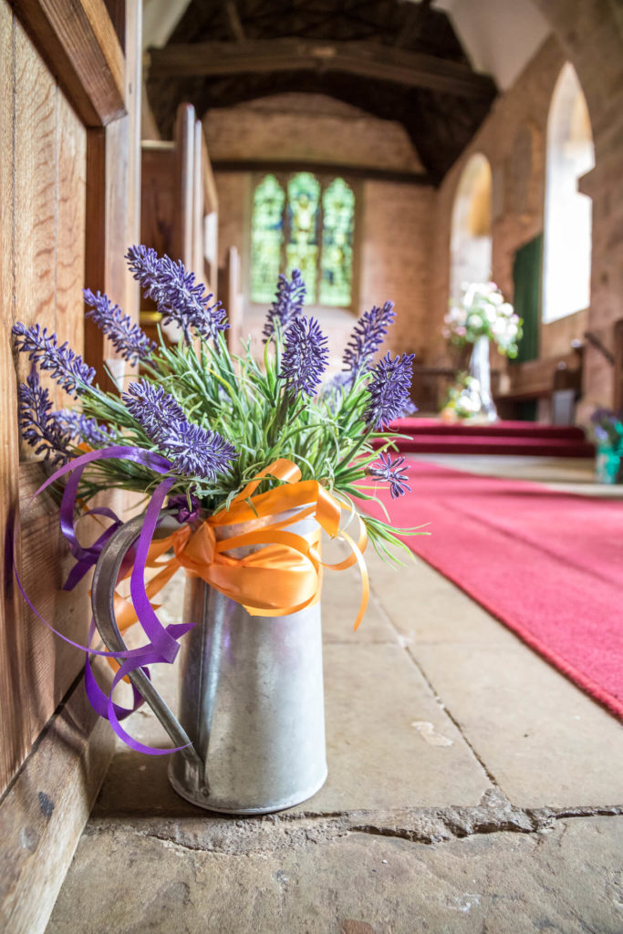 A low level shot taken inside of the church looking towards the alter of fresh lavender in an aluminium jug, which is adorned an orange ribbon and placed on the flagstone floor.