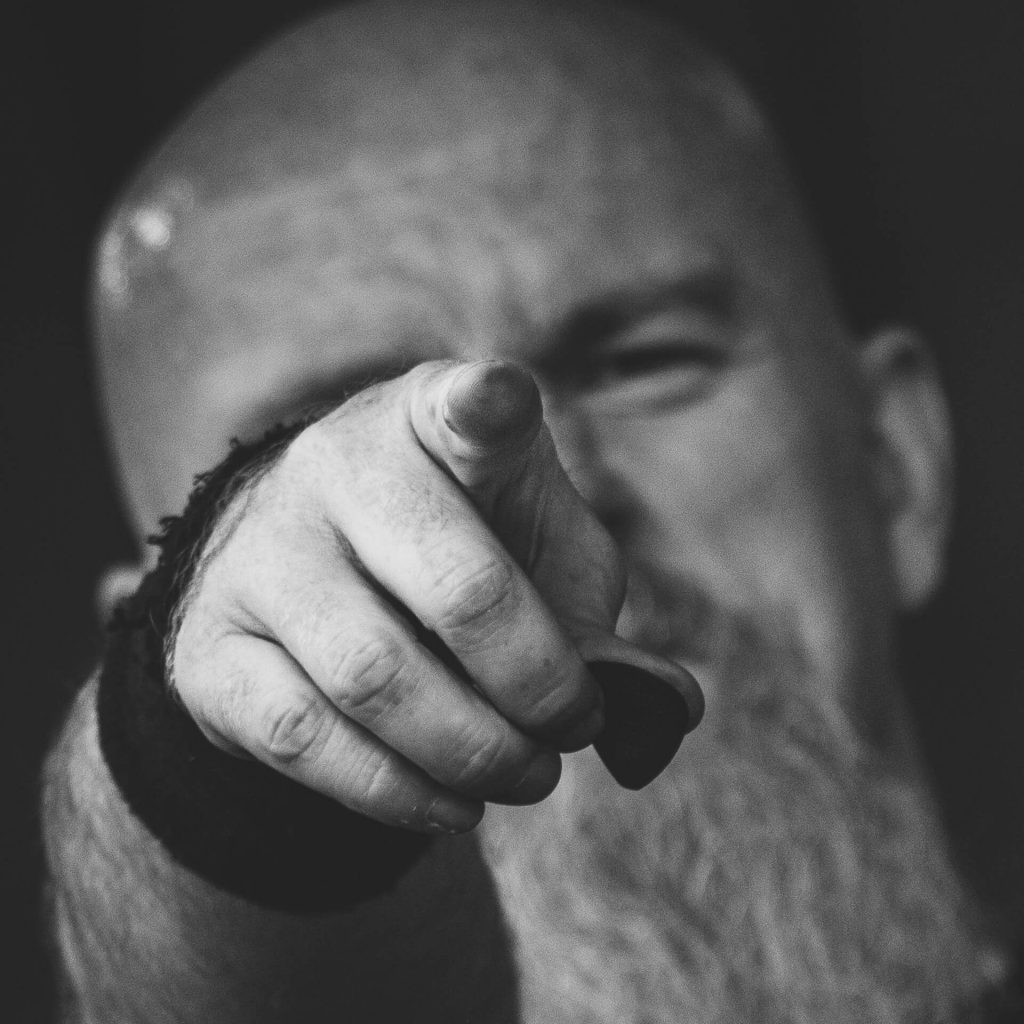 A Black & White headshot photograph of Glyn Shepherd (The Bassist in Vulcan Raine) as he points at the camera in a 'Your Country Needs You' pose at The Drunken Monkey 2017 whilst performing with Sabbotage.