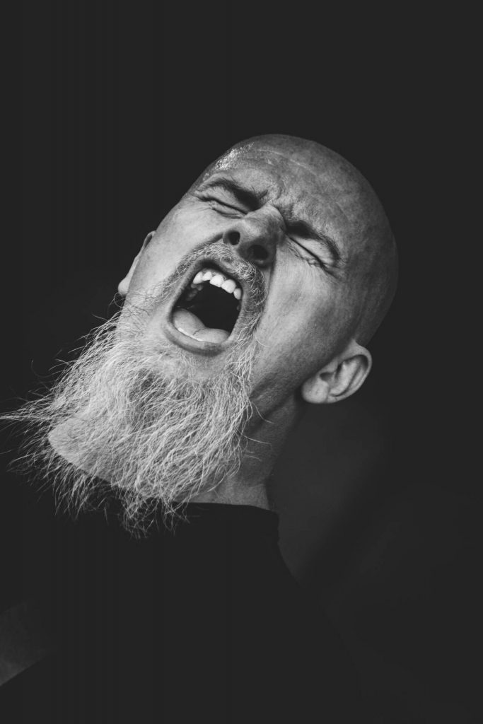 A Black & White headshot photograph of Glyn Shepherd (The Bassist in Vulcan Raine) singing on stage as part of Sabbotage at The Drunken Monkey 2017