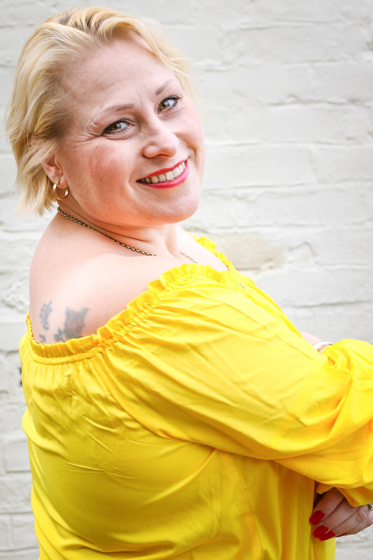 A waist up shot of Annie, a gregarious individual, who is seen stood in front of a white painted brick wall She is facing towards the wall, and she looks over her right shoulder towards the camera. Her blonde hair is cut short, she wears a vivid yellow dress which hides her more than ample cleavage She has bright red finger nails. with matching lipstick.
