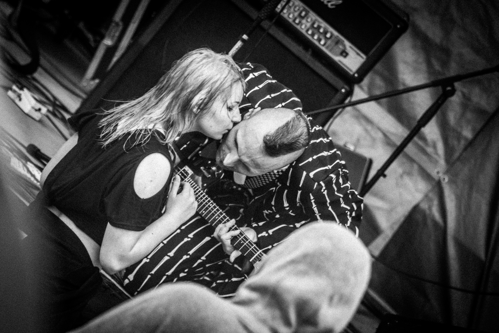 A young female member of the audience who had been dancing alone in the rain at Mappfest 2017 leans forward to give Baz Francis (lead singer of Magic 8 Ball) a kiss on the right cheek at the edge of the stage as the band continue to play
