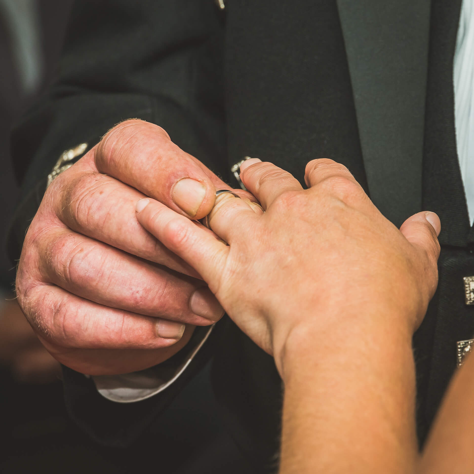 A close-up shot of the Bride and Grooms hands as he places the ring on the Brides finger.