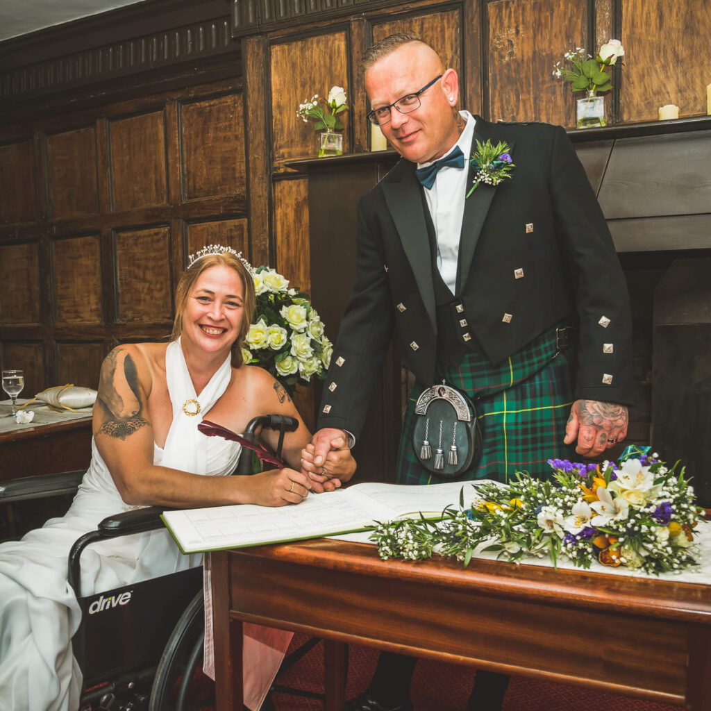 A smiling Bride sits in a wheelchair holding her new husbands hand as she signs the marriage register.