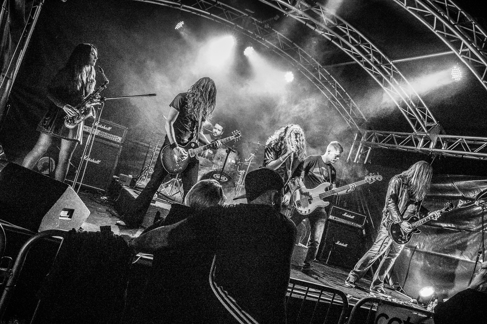 A wide angle Black & White photograph of Kikamora on stage performing at The Drunken Monkey Festival 2017.