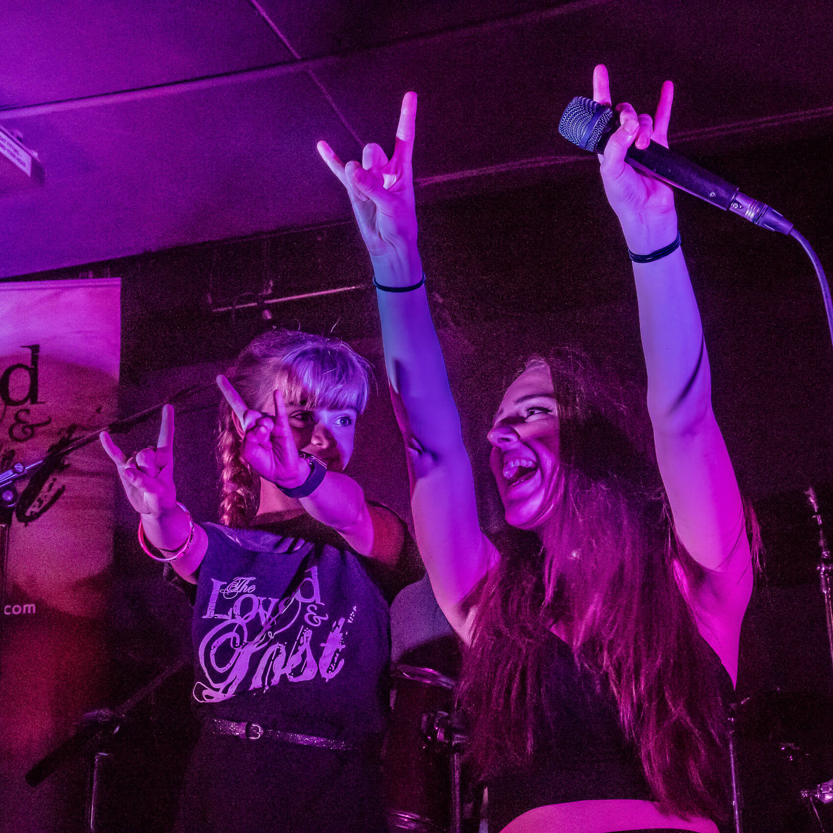 A colour photograph of a smiling young girl stood next to a kneeling and laughing Jordan Quinn (Lead singer of The Loved & Lost) whilst they both make the Heavy Metal 'Devils Horns' sign with both hands on stage during The Worcester Music Festival 2017.