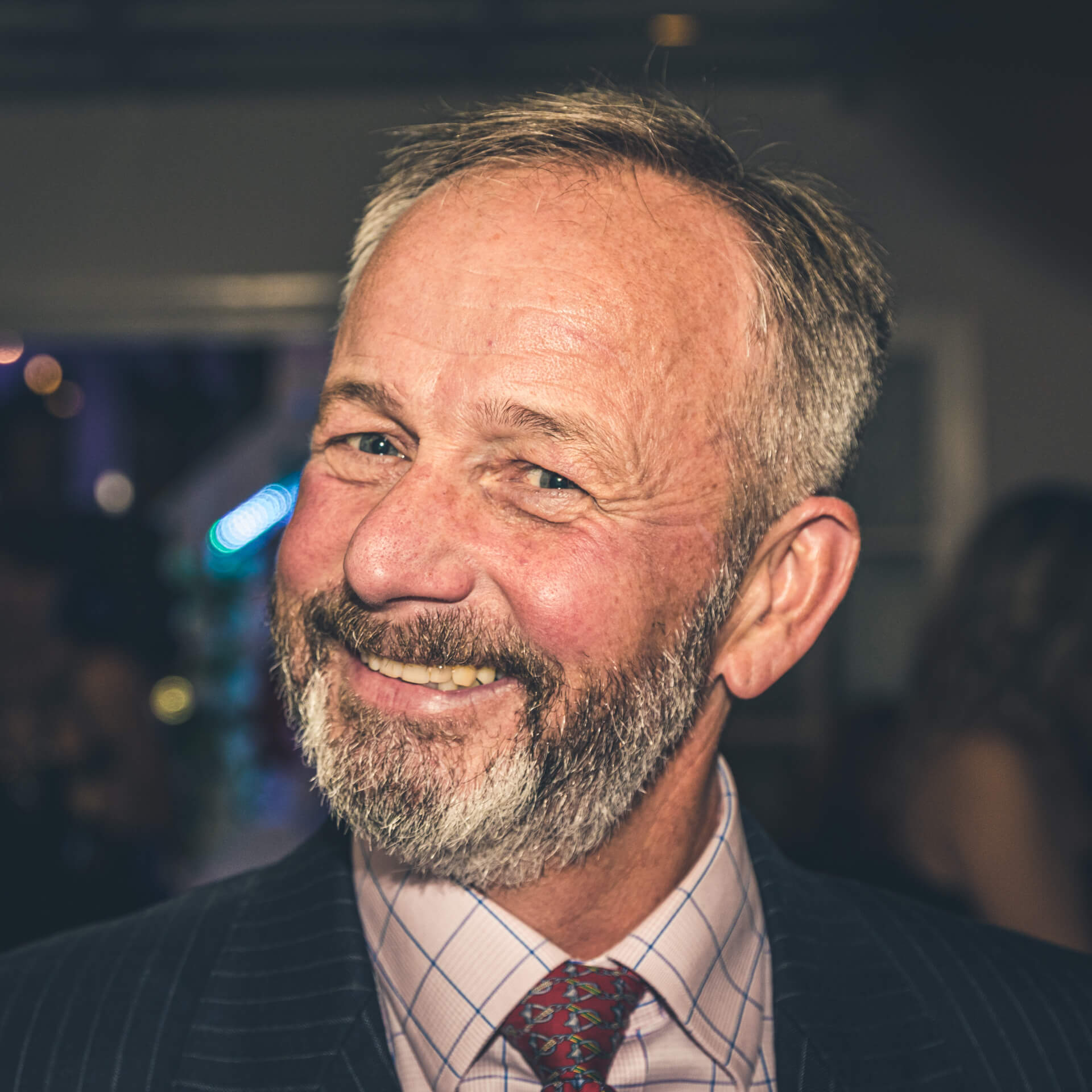 A colour head shot of a bearded and grinning Gentleman called Stewart. Stewart is married to a lady to whom I owe a huge debt of thanks for she took my daughter under her wing, encouraged her, and taught her to be a hairdresser. Taken at a friends Business Birthday Party around Christmas 2019 in Tidworth.