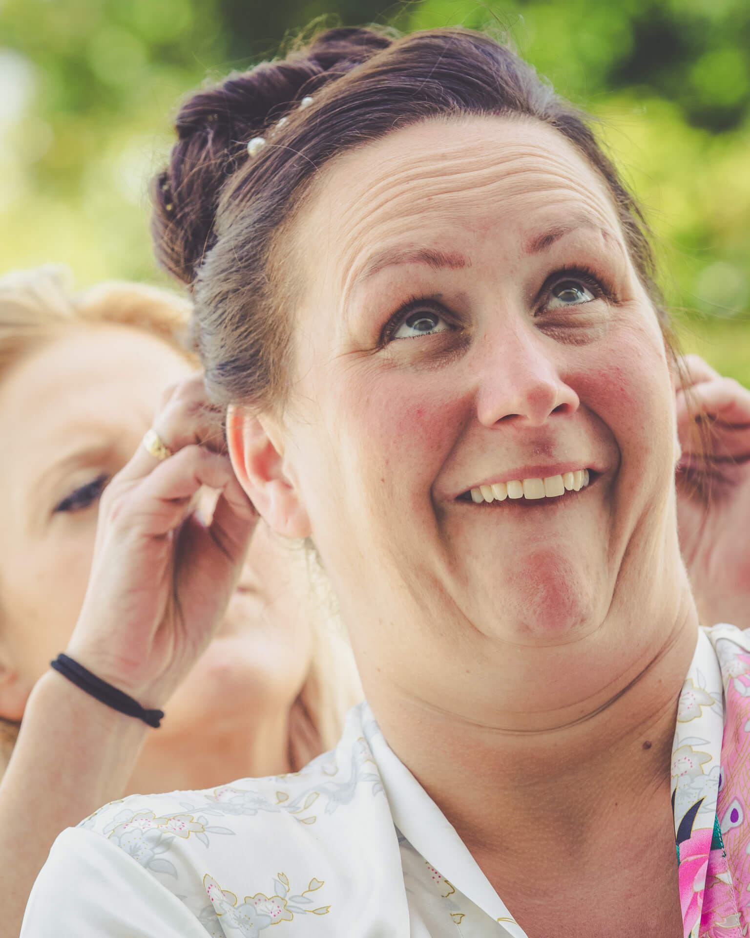 The Bride pulls a funny face whilst having her hair done as part of bridal preparations prior to the service starting.