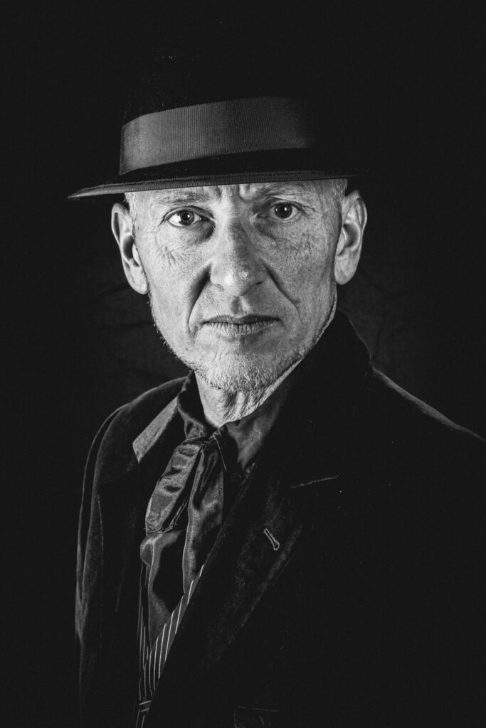 Barry 'Baz' William. Barry is the acoustic guitarist with The Julie July Band. He is seen here in a B&W head only shot. Barry were a trilby style hat, a formal jacket, a button up shirt, and a waistcoat, he looks directly into the camera.