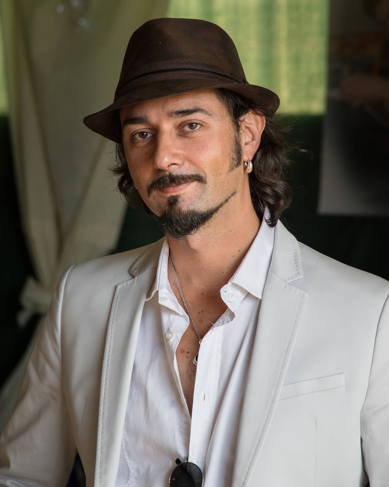An unknown male wedding guest. A hat wearing, dark curly haired, brown eyed, bearded individual he attended a wedding I was shooting at in France in 2016 . He wears a white collared shirt, a light grey jacket, a silver chain around his neck, and has matching sunglasses hanging from his semi open shirt. He sits and poses for the camera whist giving just a hint of a smile.