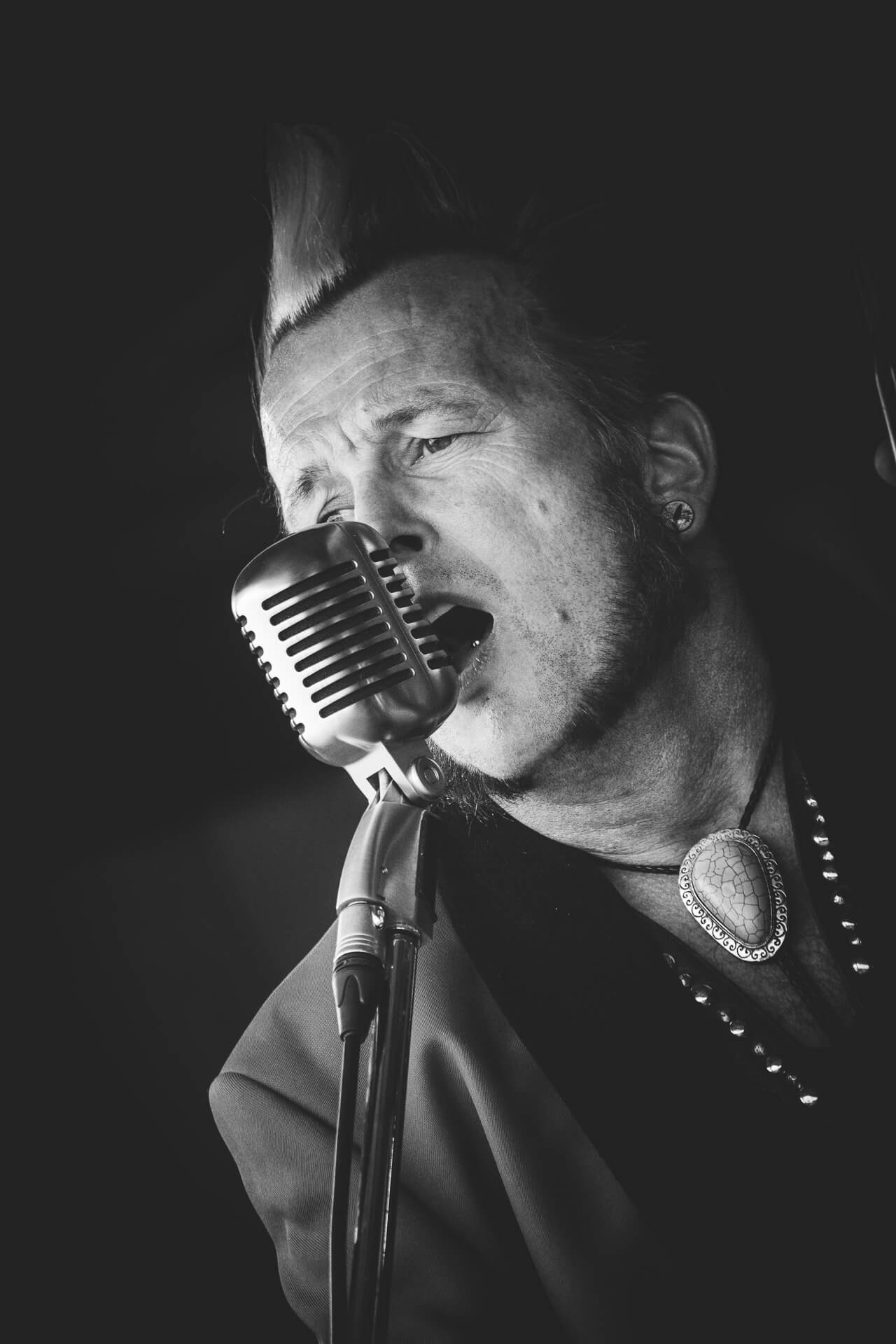 A close up Black & White photo of Gaz Le Bass of The Delray Rockets (in a drape jacket) singing into a Sure Super 55 (a 1950's style) microphone at The Drunken Monkey Festival 2017