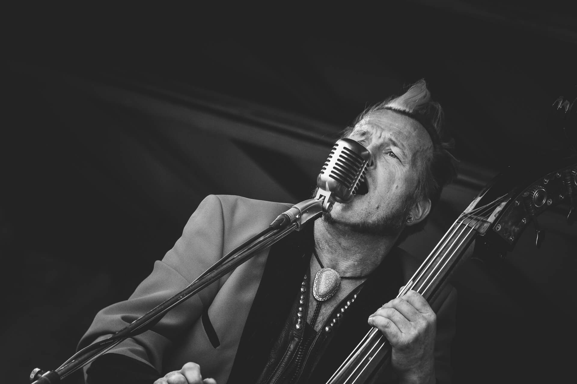 A Black & White close up photograph of Gaz Le Bass of The Delray Rockets in a drape jacket singing on stage at The Drunken Monkey Festival