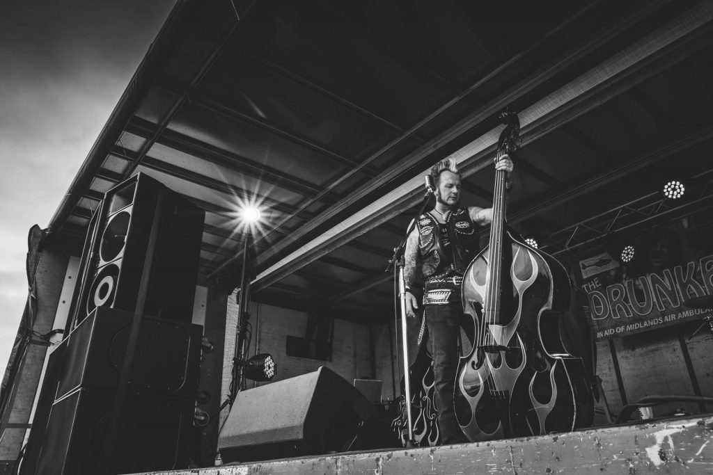 Wide angle photograph of Gaz Le Bass of The Delray Rockets holding his Upright Double Bass between songs on stage at The Drunken Monkey Festival