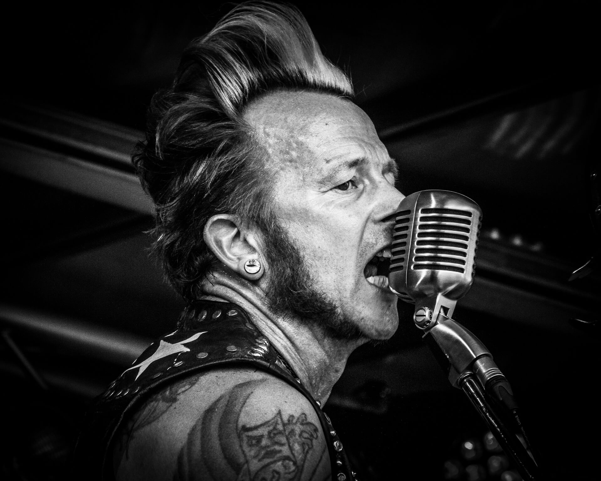 A close up Black & White photo of Gaz Le Bass of The Delray Rockets singing into a Super Sure 55 (a 1950's style) microphone at The Drunken Monkey Festival 2017
