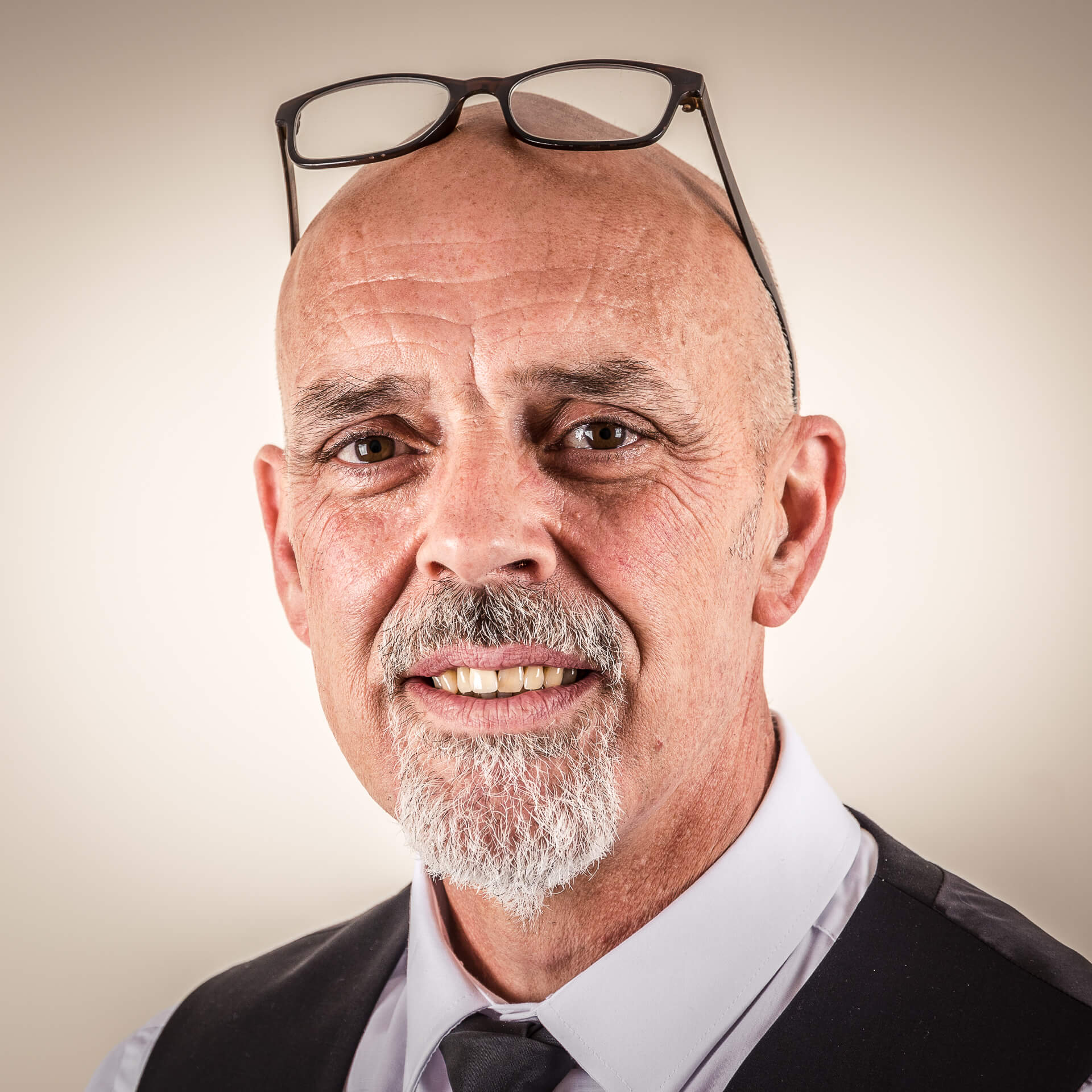 A colour head & shoulders shot of John. John used to work at Funeral Directors. John, who sports a short goatee beard, is shown here in fairly standard (save sunglasses on the top of the head) office attire for a Funeral Director, a crisp white shirt, a black tie, and a black waistcoat.