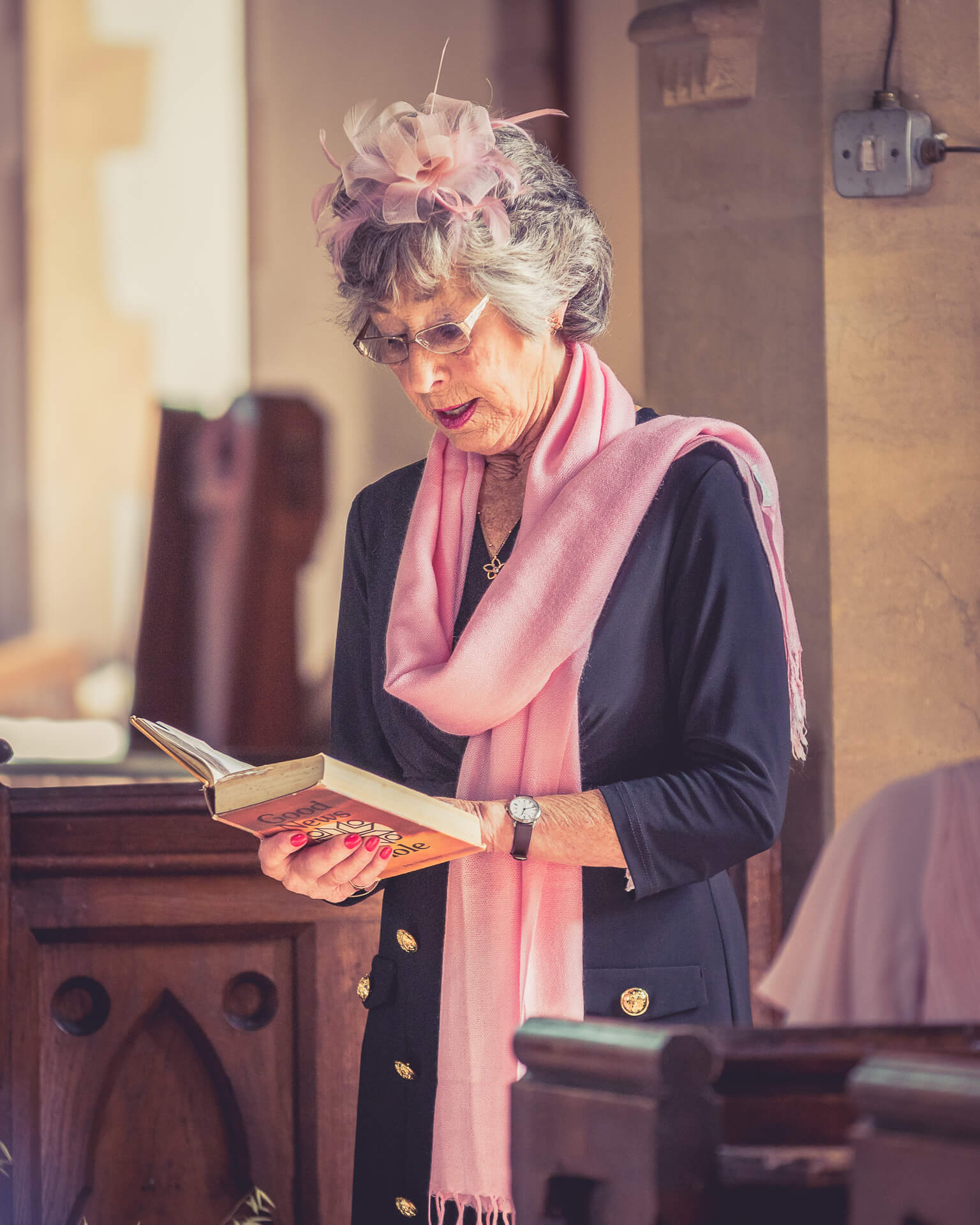 A wedding guest wearing a pink fascinator and matching scarf reads aloud to the assembled guests from the Good News Bible.