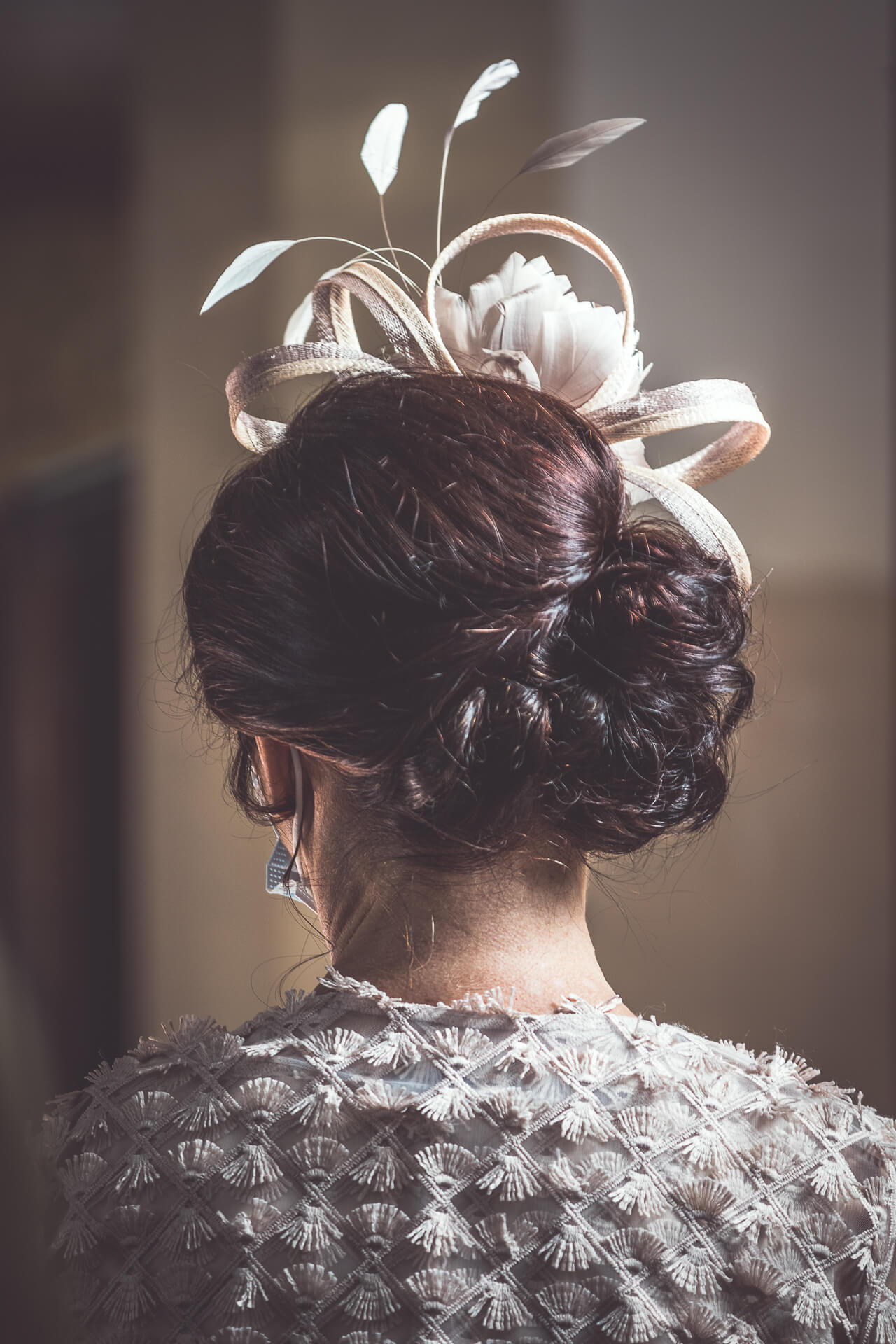 Taken from behind this is a head & shoulders image of the Mother of the Bride. Her hair is put up, and she wears a fascinator.