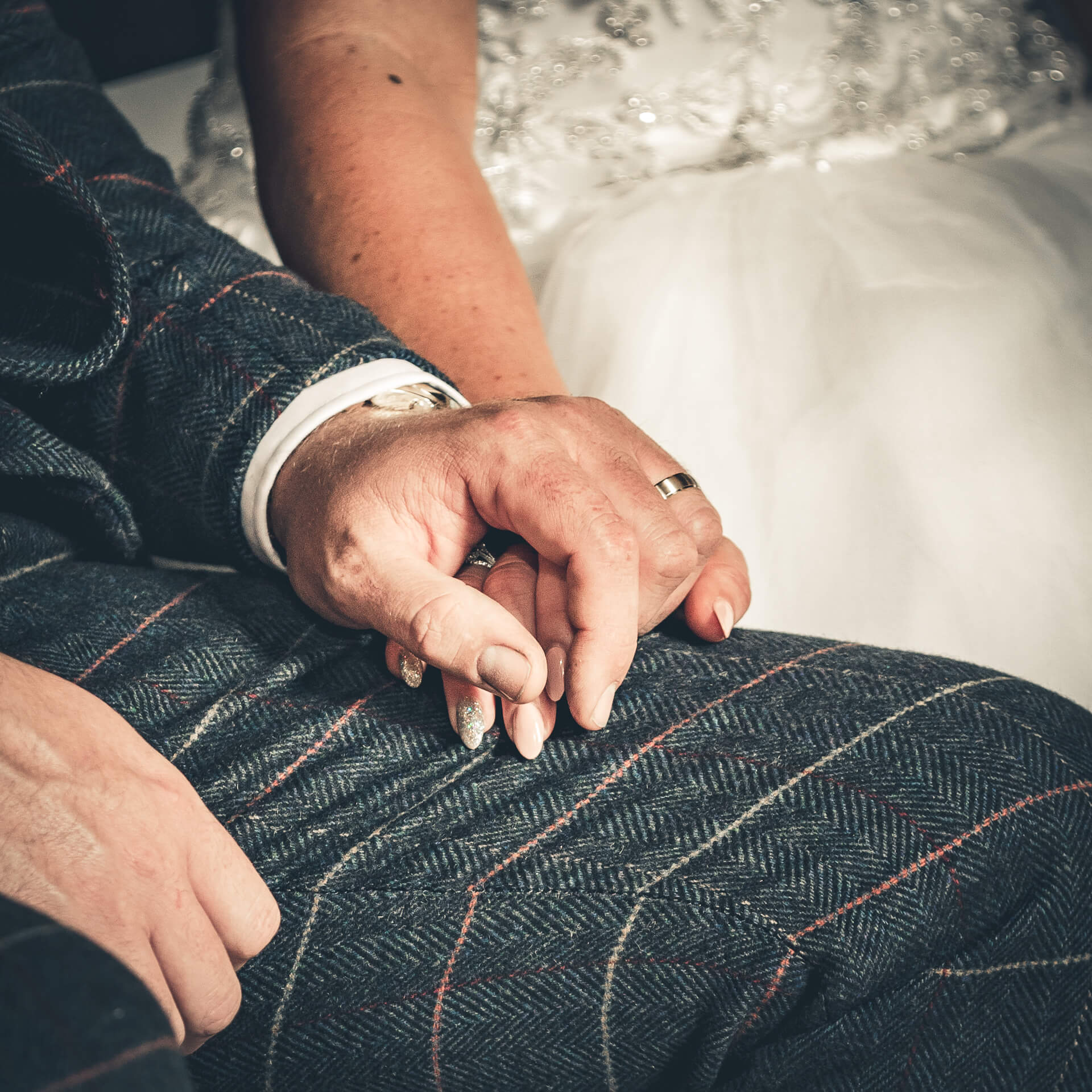 A close up shot of the Grooms thigh. The bride has placed her hand on his thigh, his hand, wearing his wedding ring, is over the top of hers.